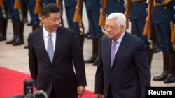 Chinese President Xi Jinping, left, acknowledges Palestinian President Mahmoud Abbas as they walk together during a welcome ceremony at the Great Hall of the People in Beijing, July 18, 2017.