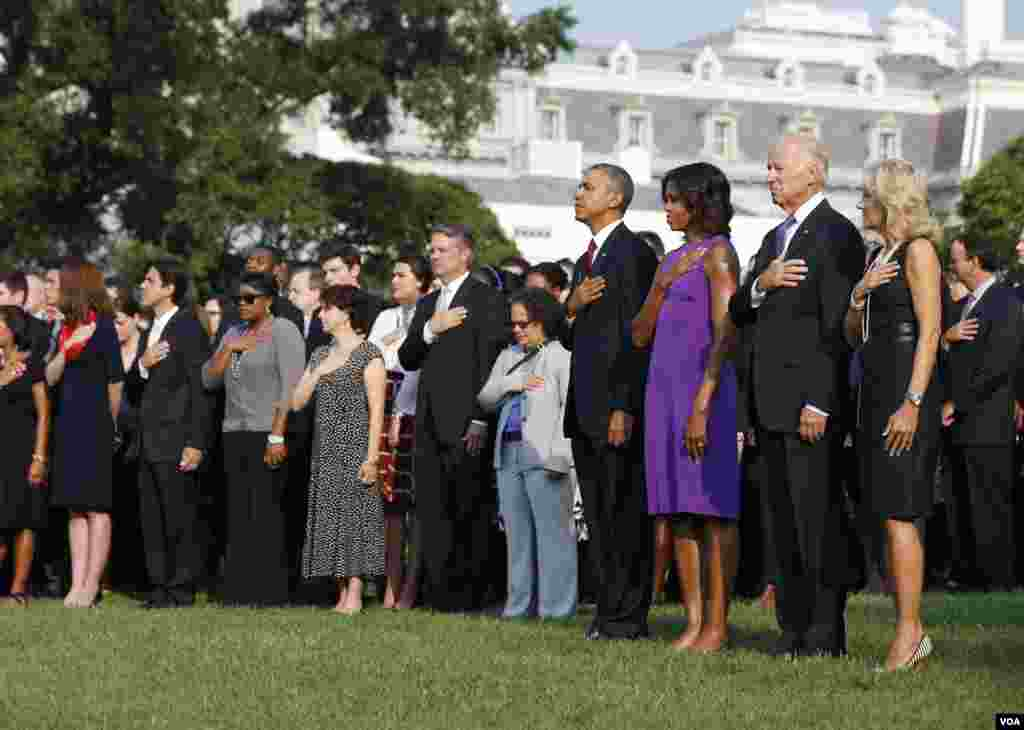 U.S. President Barack Obama, first lady Michelle Obama, Vice President Joe Biden and Jill Biden (L-R) pause for a moment of silence on the 12th anniversary of the attacks of September 11, 2001, on the South Lawn of the White House in Washington.