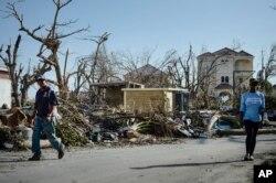 Warga berjalan melalui jalan-jalan dan rumah-rumah yang hancur setelah dihantam oleh Badai Irma, di Phillipsburg, St. Martin, 11 September 2017.
