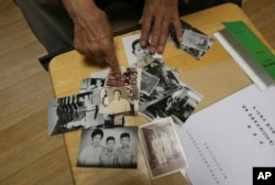 Lee Soo-nam, 76, explains the photos showing his family members during an interview at his home in Seoul, South Korea, Aug. 17, 2018. Lee is among about 200 war-separated South Koreans and their family members who are crossing into North Korea for heart-wrenching meetings with relatives they haven't seen for decades.