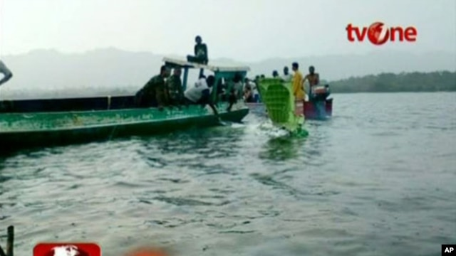 People remove debris of a plane, that had crashed into the sea off Papua province, from the water in this still image taken from video, May 7, 2011