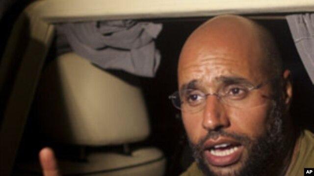 Moammar Gadhafi's son, Seif al-Islam speaks outside of the Rixos hotel in Tripoli, Libya, Tuesday, Aug. 23, 2011.
