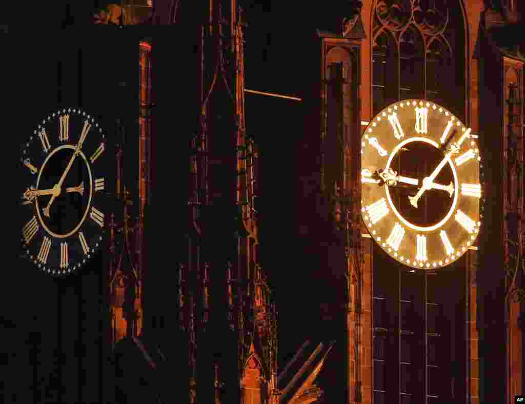 Sun light shines on one of the clocks on the cathedral in Frankfurt, Germany, on a cold and sunny day.