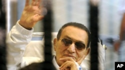 Former Egyptian President Hosni Mubarak waves to his supporters from behind bars as he attends a hearing in his retrial on appeal in Cairo, April 13, 2013.