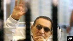 Mantan Presiden Mesir, Hosni Mubarak, melambaikan tangan kepada para pendukungnya, saat menghadiri sidang di pengadilan Kairo (13/4).