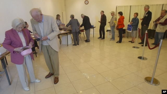 French citizens line up to vote during legislative election in Louveciennes , 12 kms ( 7.5 mls) west of Paris, June 17, 2012.