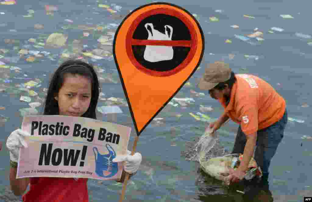 A young environmental activist holds a placard calling for a ban of the use of plastic bags, in Manila, Philippines, while rubbish is removed (R) from the bay.