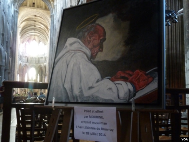 A painting of the late Father Jacques Hamel, the Catholic priest killed by jihadists while celebrating Mass at his church in St. Etienne du Rouvray, hangs at Rouen's cathedral. The painting was done by Moubine, a Muslim artist. (L. Ramirez/VOA)