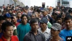 Para nelayan Myanmar menunggu waktu keberangkatan dari kompleks perusahaan perikanan Pusaka Benjina Resources di Benjina, Kepulauan Aru (3/4). (AP/Dita Alangkara)