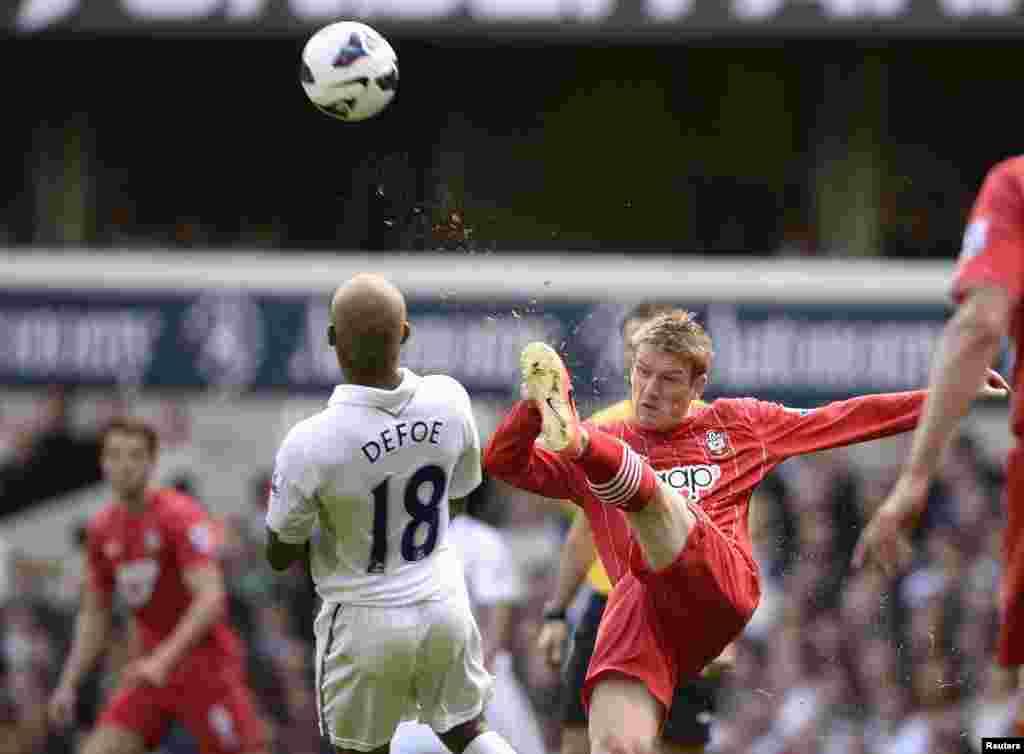 Tottenham Hotspur's Jermain Defoe (L) challenges Southampton's Steven Davis for the ball during their English Premier League soccer match at White Hart Lane in London.
