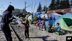 Grčki policajac daje papir s informacijama detetu u improvizovanom kampu na severu zemlje, u blizini Idomenija