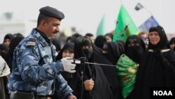 An Iraqi policeman uses a bomb detector to search Shi'ite pilgrims heading to the Shi'ite holy city of Kerbala, 80 kilometers (50 miles) south of Baghdad, Dec. 10, 2014.