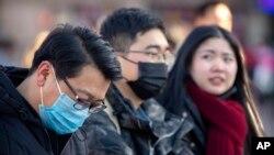 مسافران با ماسک منتظر قطار در پکن، چین - ۲۰ ژانویه ۲۰۲۰