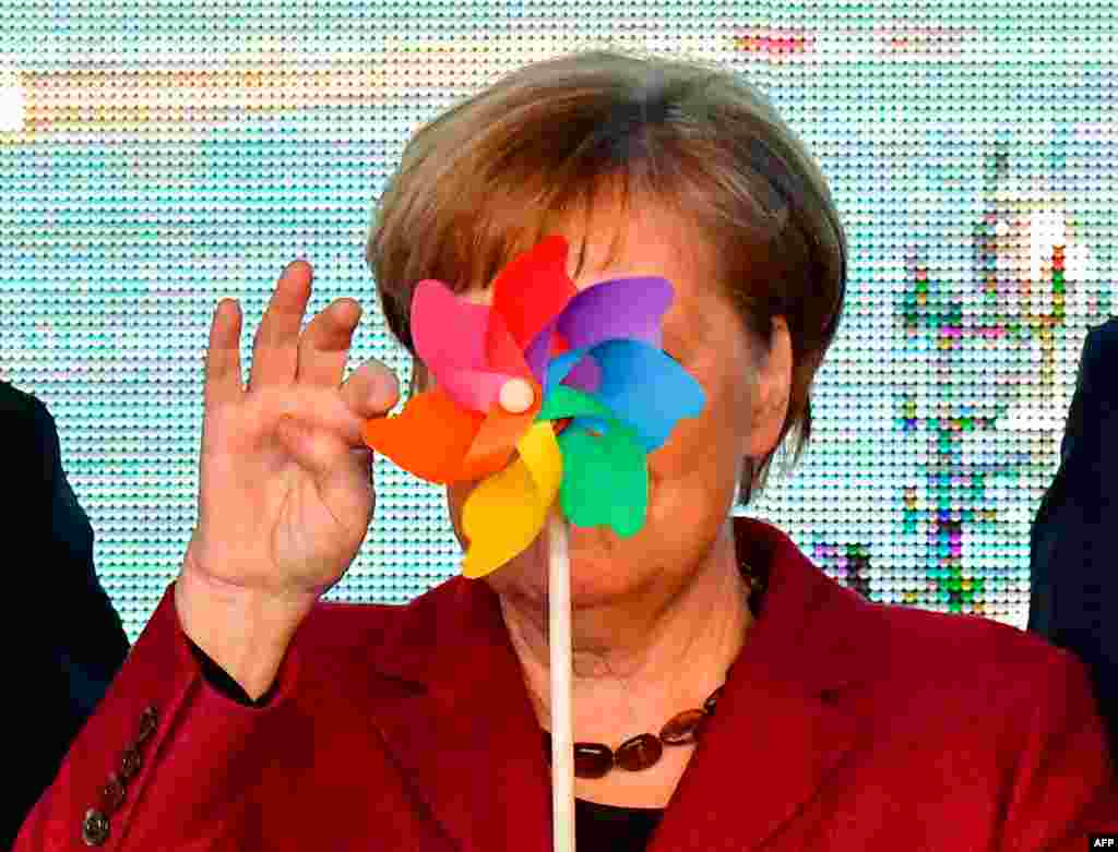 German Chancellor Angela Merkel is partly hidden by a toy wind wheel as she poses with children during the opening ceremony of the Arkona wind park in Sassnitz, northern Germany.