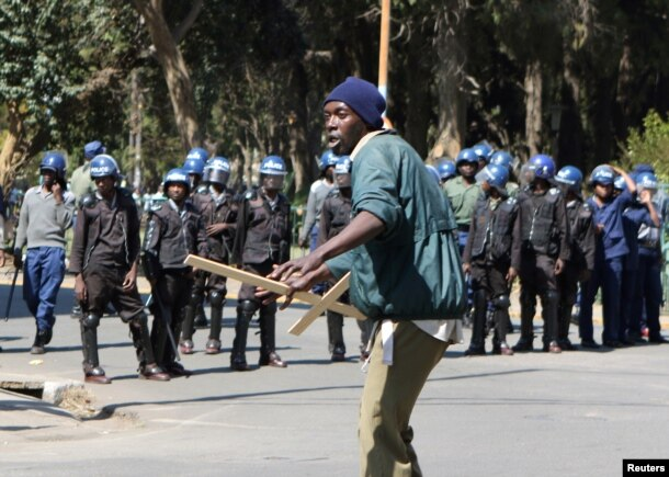 A demonstrator reacts after anti-riot police use batons to break up a peaceful march protesting the Zimbabwe government's handling of the economy, in Harare, Aug. 3, 2016.