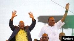Perezida wa Afrika y'Epfo Jacob Zuma (ibubamfu) aramutsa abanywanyi biwe ari kumwe na Perezida wa Kenya Uhuru Kenyatta igihe ANC wibuka imyaka 106 ushinzwe, East London, Afrika y'Epfo, Ukwezi kwa mbere, itariki 13, 2018