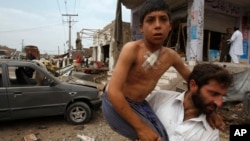 Pakistani man helps injured boy at site of car bombing on outskirts of Peshawar, Pakistan, June 30, 2013.