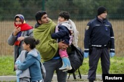 FILE - A migrant family approaches a registration center at a Croatia-Slovenia border crossing in Lendava, Slovenia, Oct. 17, 2015.
