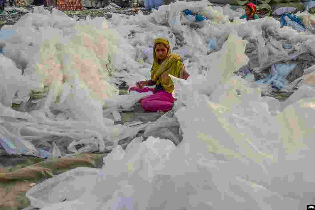 A worker gathers and sorts plastic bags used to carry industrial chemicals to dry by the Buriganga river in Dhaka, Bangladesh.