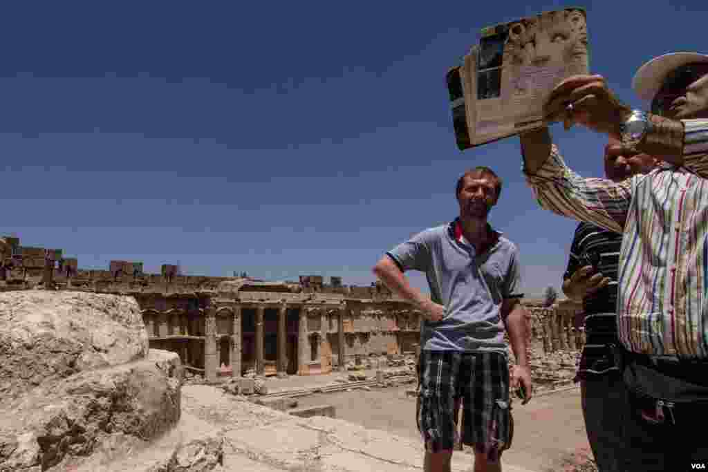 A tour guide shows Danish engineer Hans Brink (second from left) and a colleague around the Roman ruins. (John Owens for VOA News)