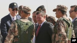 Jordan's King Abdullah II, center, and U.S. Vice President Joe Biden, left, visit a joint Jordanian-American training center at Zarqa, northeast of Amman, Jordan, March 10, 2016.