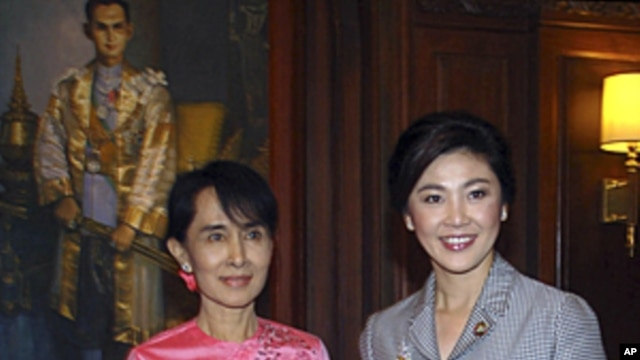 Thai Prime Minister Yingluck Shinawatra, right, stands with Myanmar pro-democracy leader Aung San Suu Kyi during a meeting at the Thai Embassy in Yangon, Myanmar, December 20, 2011.