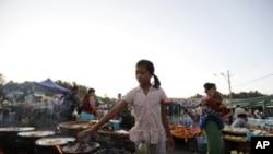 一名緬甸女孩在市場上烹飪快餐