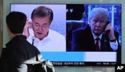 FILE - A man walks by a TV screen showing a local news program reporting about North Korea's missile launch with an images of U.S. President Donald Trump and South Korean President Moon Jae-in at the Seoul Railway Station in Seoul, South Korea, Dec. 1, 2017.