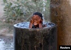 Bé gái tắm dưới một đường ống nước bị rỉ ở vùng ngoại ô Ahmedabad, Ấn Độ. nhiệt độ hằng ngày có ngày lên tới 48 độ C, là lúc mà con số các ca tử vong tăng vọt.