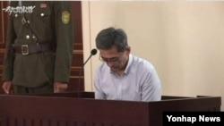 북한은 24일 대남용 매체인 우리민족끼리TV를 통해 남한 국민 김국기·최춘길 씨에게 '무기노동교화형'(무기징역)을 선고한 재판 과정이 담긴 동영상을 공개했다. 사진은 김국기 씨가 자신의 죄를 읽는 모습으로, 그는 내용을 숙지하지 못한 듯 문장을 읽는 도중에 종종 말을 멈췄다.