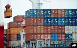 FILE - A container is loaded onto a cargo ship at the Tianjin port in China.