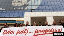 Employees of the Bank of Cyprus take part in a rally, in solidarity with crisis-hit Cypriots, outside the headquarters of the bank in Athens, Greece, Mar. 20, 2013.