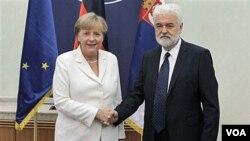 Kanselir Jerman Angela Merkel (kiri) berjabat tangan dengan PM Serbia Mirko Cvetkovic saat berkunjung ke Belgrade, Serbia (23/8).
