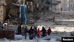 Người dân Syria bước trên các đống đổ nát, mang theo đồ đạc, chạy tránh các cuộc đụng độ giữa lực lượng chính phủ và phe nổi dậy ở khu vực đông Aleppo, Syria, 28/11/2016.