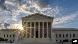 The sun flares in the camera lens as it rises behind the U.S. Supreme Court building in Washington, June 25, 2017.