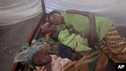 FILE - Two children and their mother rest under a mosquito net.