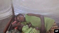 Une mère et ses enfants, protégés par une moustiquaire imprégnée