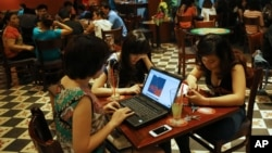 Three young Vietnamese girls use a laptop and smart phones to go online at a cafe in Ha Noi, Viet Nam Wednesday, May 14, 2013. (AP Photo/Na Son Nguyen)