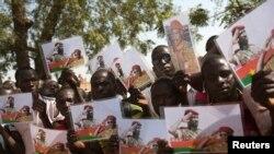 Des Burkinabès tiennent des photos de l'ancien président Thomas Sankara et du premier ministre Isaac Zida à Ouagadougou, le 2 décembre 2014.