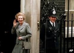 FILE - Britain's Prime Minister Margaret Thatcher waves to members of the media on returning to No. 10 Downing Street from Buckingham Palace after a visit with Queen Elizabeth II, May 11, 1987.