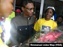 De retour au Cameroun, Rigobert Song reçoit un bouquet de fleurs à sa descente d'avion à l'aéroport international de Yaoundé Nsimalen, 1er avril 2017. (VOA/Emmanuel Jules Ntap)
