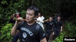 Pripadnici malezijske policije nose vreće sa posmrtnim ostacima migranata
