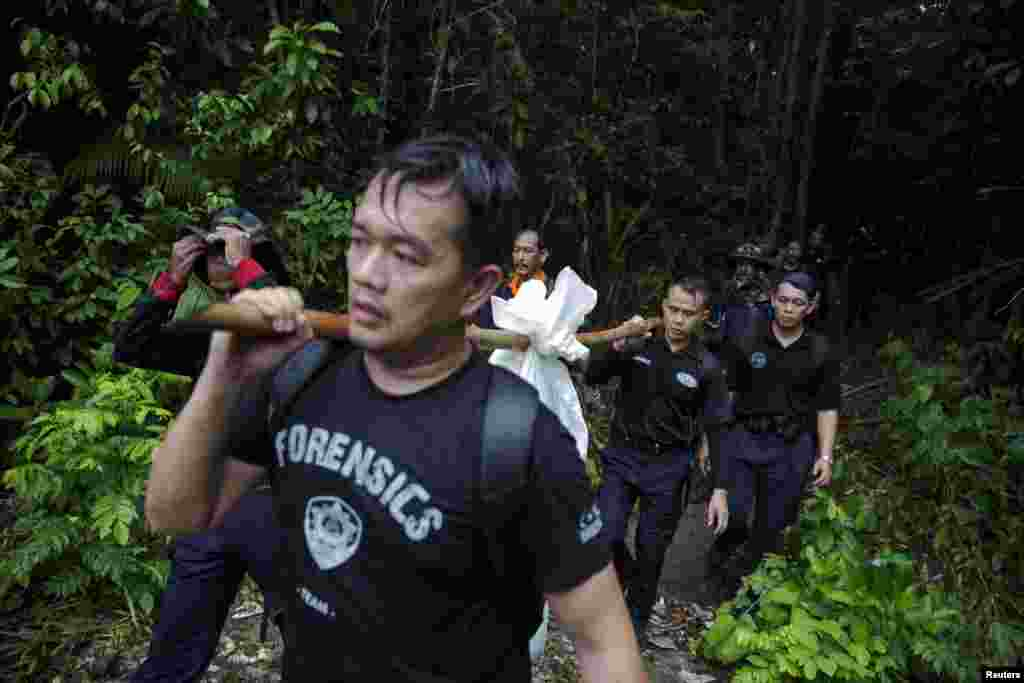 Members of a police forensic team carry a body bag with human remains dug from a grave near the abandoned human trafficking camp in the jungle close to the Thailand border at Bukit Wang, Burma, in northern Malaysia, May 27, 2015.
