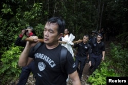 Members of a police forensic team carry a body bag with human remains dug from the grave near the abandoned human trafficking camp in the jungle close the Thailand border at Bukit Wang Burma in northern Malaysia , May 27, 2015.