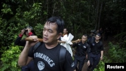 Members of a police forensic team carry a body bag with human remains dug from the grave near the abandoned human trafficking camp in the jungle close the Thailand border at Bukit Wang Burma in northern Malaysia May 27, 2015. Malaysian police forensic tea