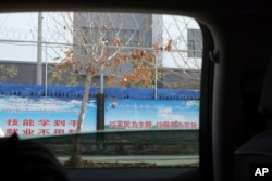 """In this Dec. 5, 2018, photo, slogans which reads """"Technical skill in hand, No worries finding a job,"""" are seen on the barbed wire fences around the """"Hotan City apparel employment training base"""" where Hetian Taida has a factory in Hotan."""