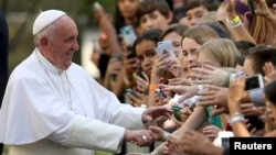 Pope Francis greets schoolchildren upon departing the Vatican Embassy in Washington. In the midst of his six-day trip, he moves on to New York for more outreach, Sept. 24, 2015.