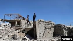 Des hommes inspectent une maison endommagée à Busra al-Harir, près de Deraa, en Syrie, le 13 mars 2018.
