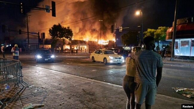 2020年5月28日,美国明尼阿波利斯骚乱事件中抗议者注视一家汽车零件商店在燃烧。