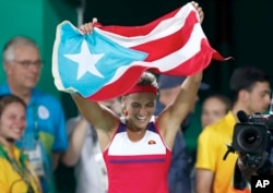 Monica Puig of Puerto Rico celebrates holding her country's flag after winning the gold medal match in the women's tennis competition at the 2016 Summer Olympics in Rio de Janeiro, Brazil, Saturday, Aug. 13, 2016.